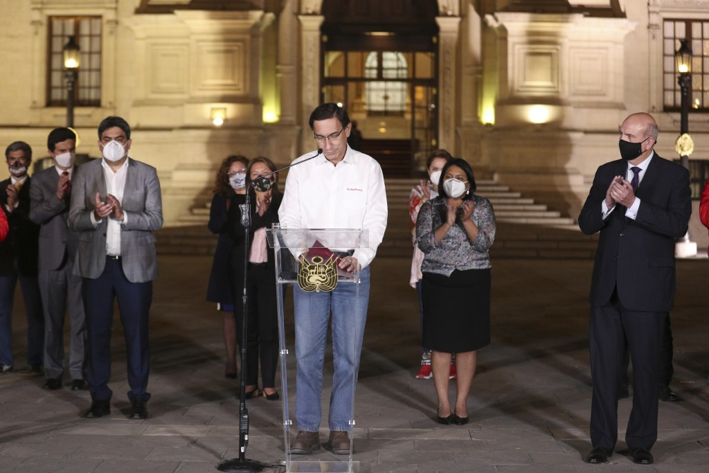 Peru's President Martin Vizcarra looks down as members of his cabinet applaud in front of the presidential palace after lawmakers voted to remove him ...