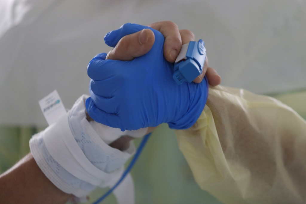 FILE - In this Friday, Oct. 30, 2020 filer, therapist Catia Jesus holds the hand of a patient inside a COVID-19 ICU at Santa Maria hospital in Lisbon....