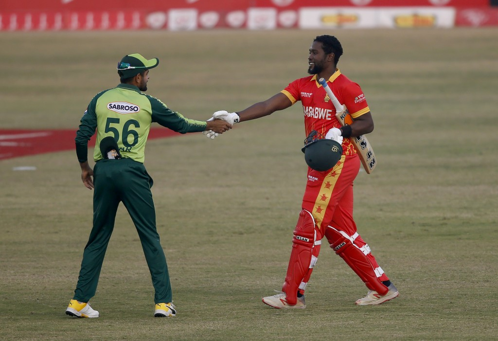 Pakistan's skipper Babar Azam, left, greets Zimbabwe's batsman Elton Chigumbura, who arrives to play his last match during their 3rd Twenty20 cricket ...