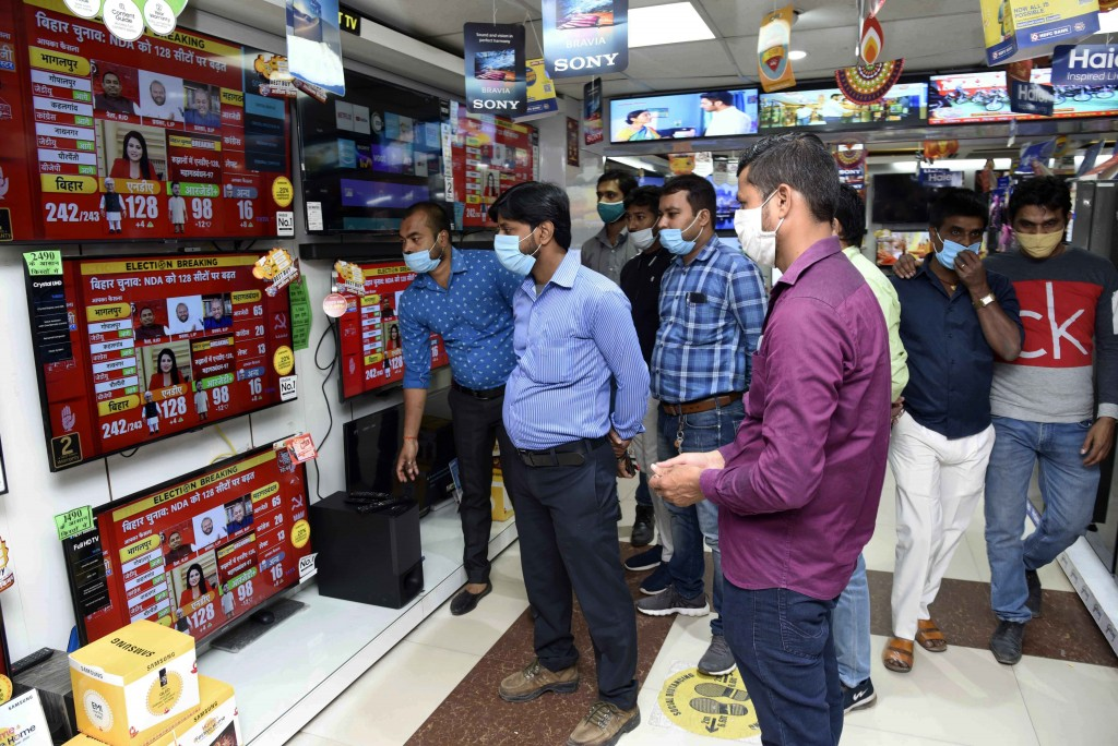 People watch news of Bihar state assembly election results at an electronics shop in Patna, India, Tuesday, Nov. 10, 2020. (AP Photo/Aftab Alam Siddiq...
