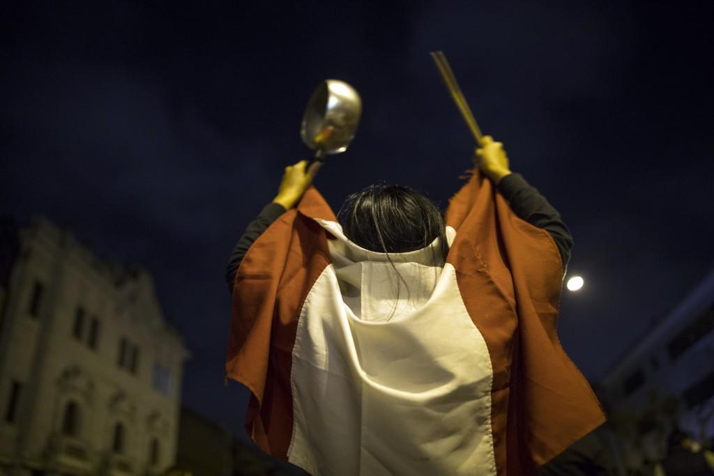 A pro-government protester hits a pot during a protest near the Congress in Lima, Peru, Monday, Nov. 9, 2020. (AP Photo/Rodrigo Abd)