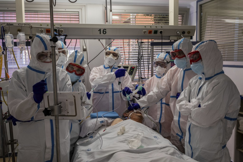 FILE - In this Friday, Oct. 9, 2020 filer, a patient infected with COVID-19 is treated in one of the intensive care units (ICU) at the Severo Ochoa ho...