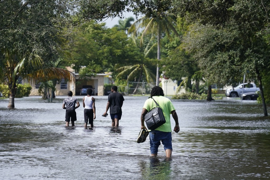 Residents walk a flooded street to reach their homes, Monday, Nov. 9, 2020 in Fort Lauderdale, Fla. Tropical Storm Eta caused severe flooding in South...