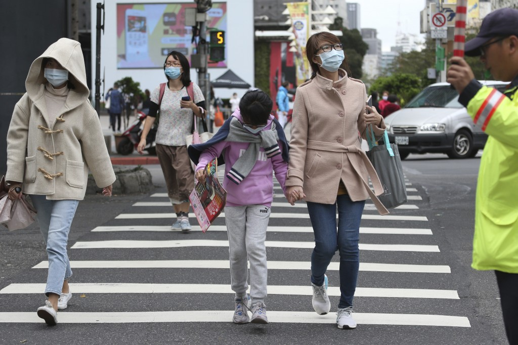 People cross an intersection wearing face masks to protect against the spread of the coronavirus in Taipei, Taiwan, Tuesday, Nov. 10, 2020. (AP Photo/...