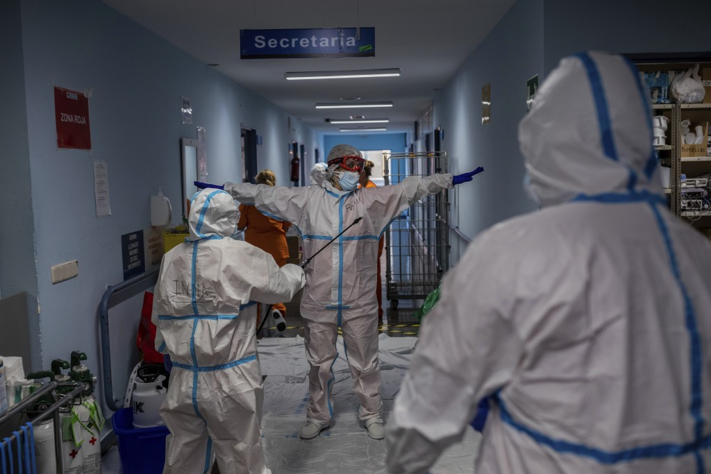 A medical team member is disinfected before leaving the COVID-19 ward at the Severo Ochoa hospital in Leganes, outskirts of Madrid, Spain, Friday, Oct...