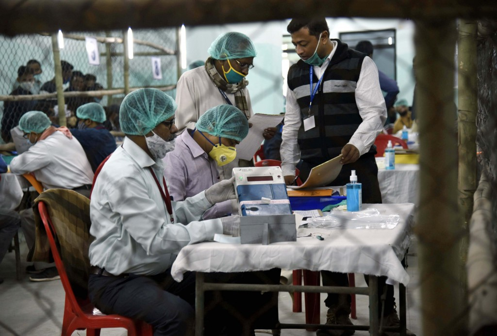Election officers wearing face masks count votes for the Bihar state assembly polls, at a counting centre in Patna, India, Tuesday, Nov. 10, 2020. (AP...