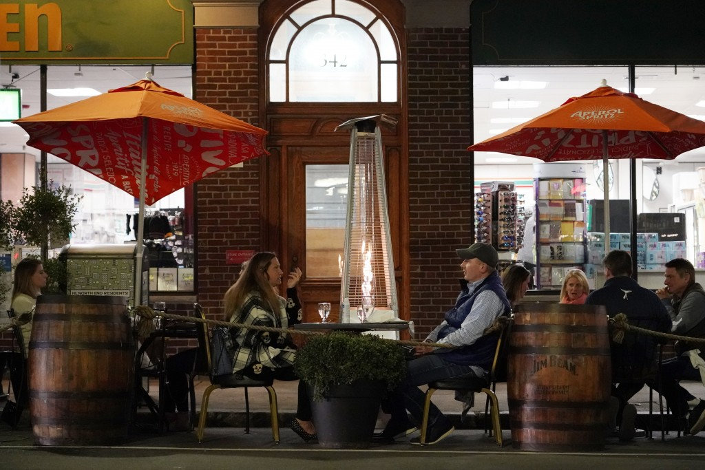 FILE - In this Nov. 6, 2020, file photo, patrons eat dinner outdoors in Boston's North End. More stringent coronavirus restrictions are now in effect ...