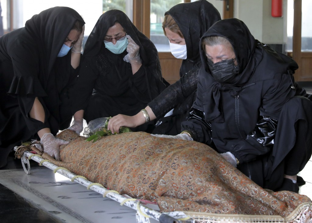 Relatives mourn over the body of a person who died from COVID-19 at the Behesht-e-Zahra cemetery just outside Tehran, Iran, Sunday, Nov. 1, 2020. The ...
