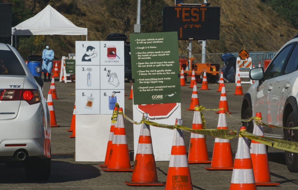 FILE - In this Nov. 9, 2020, file photo, instructions to perform a COVID-19 virus self-test are displayed for drivers at Dodger Stadium, with the capa...