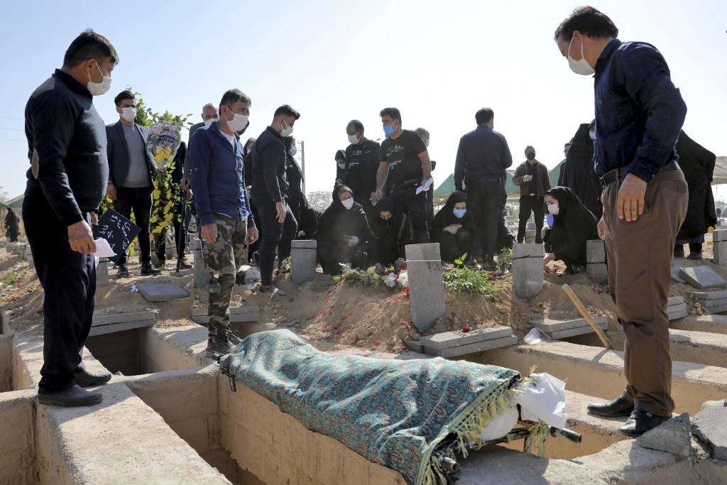Mourners attend the funeral of a person who died from COVID-19 at the Behesht-e-Zahra cemetery on the outskirts of Tehran, Iran, Sunday, Nov. 1, 2020....