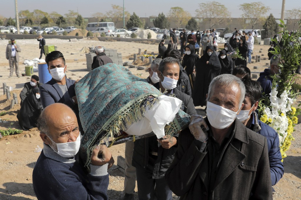 Mourners carry the body of a person who died from COVID-19, at the Behesht-e-Zahra cemetery on the outskirts of Tehran, Iran, Sunday, Nov. 1, 2020. Th...