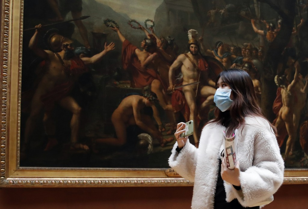 FILE - In this file photo dated Thursday, March 5, 2020, masked tourist walks by an oil on canvas of 1814 entitled Leonidas at Thermopylae, by Jacques...