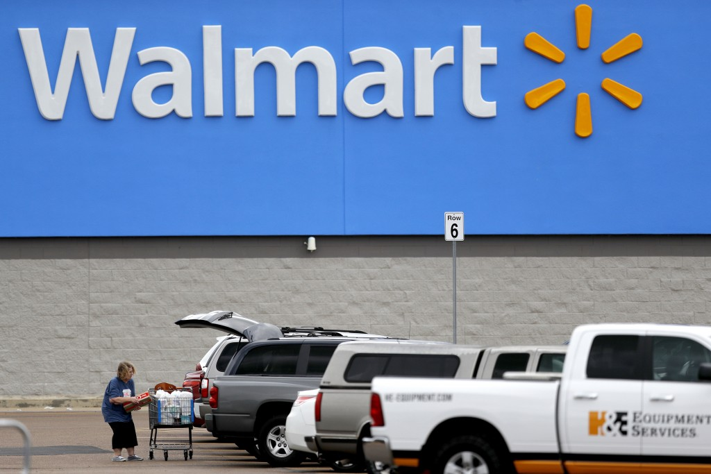FILE - In this March 31, 2020 file photo, a woman pulls groceries from a cart to her vehicle outside of a Walmart store in Pearl, Miss. Walmart is tea...
