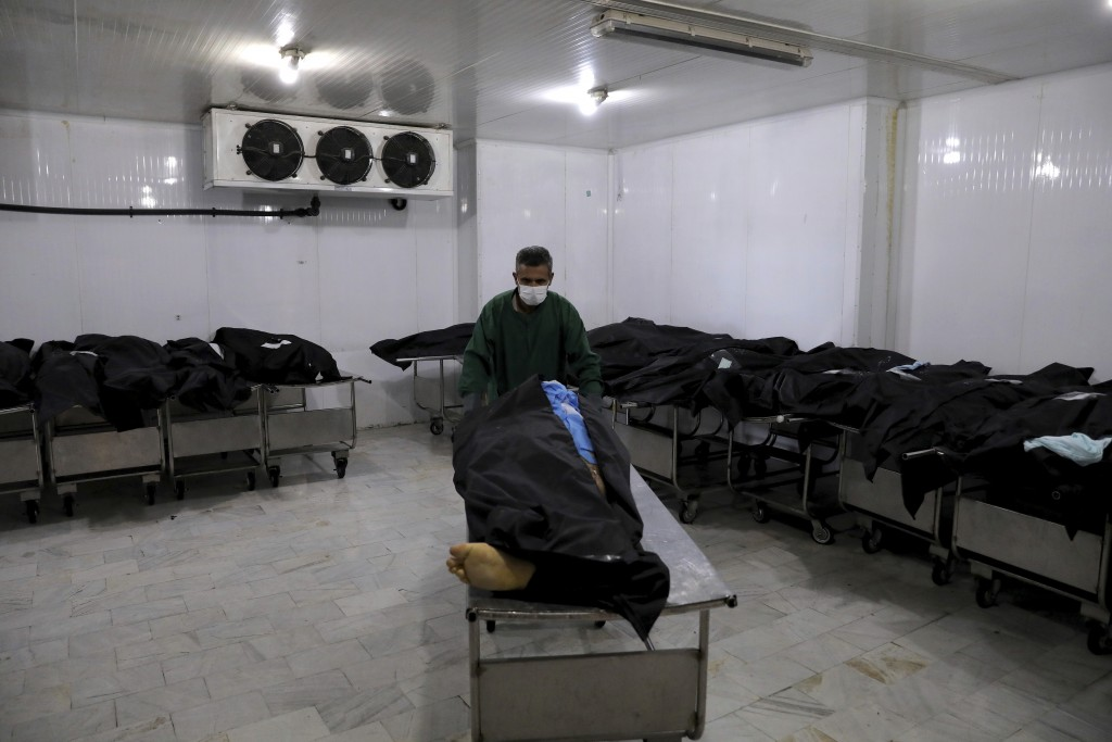 An Iranian cemetery worker prepares the body of a man who died from COVID-19, in a morgue at the Behesht-e-Zahra cemetery on the outskirts of the Iran...