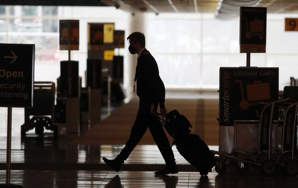 FILE - In this Thursday, April 9, 2020, file photo, a lone airline crew member pulls his bags behind him as he walks through the baggage-claim area at...