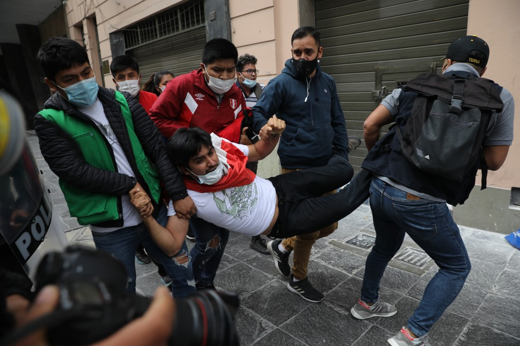 Police in civilian clothes detain a supporter of former President Martin Vizcarra as he and other protesters are blocked from reaching Congress to pro...