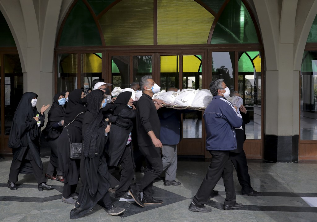 Mourners carry the body of a person who died from COVID-19, at the Behesht-e-Zahra cemetery on the outskirts of the Iranian capital, Tehran, Iran, Sun...