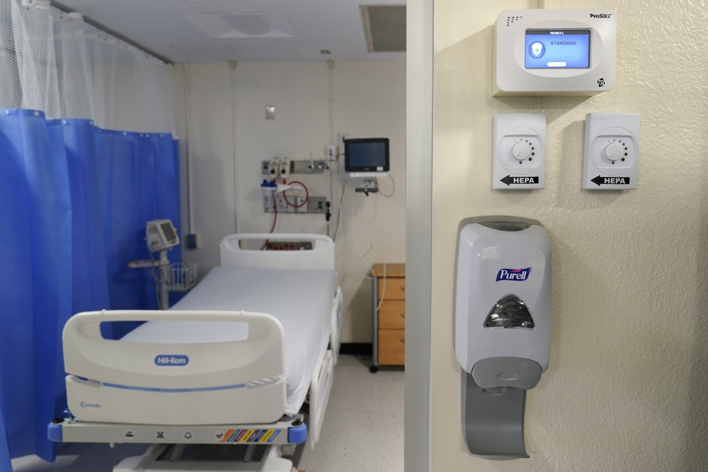 FILE - This Oct. 28, 2020, file photo shows new machinery, right, that helps to turn a regular hospital room into an isolation room at Bellevue Hospit...