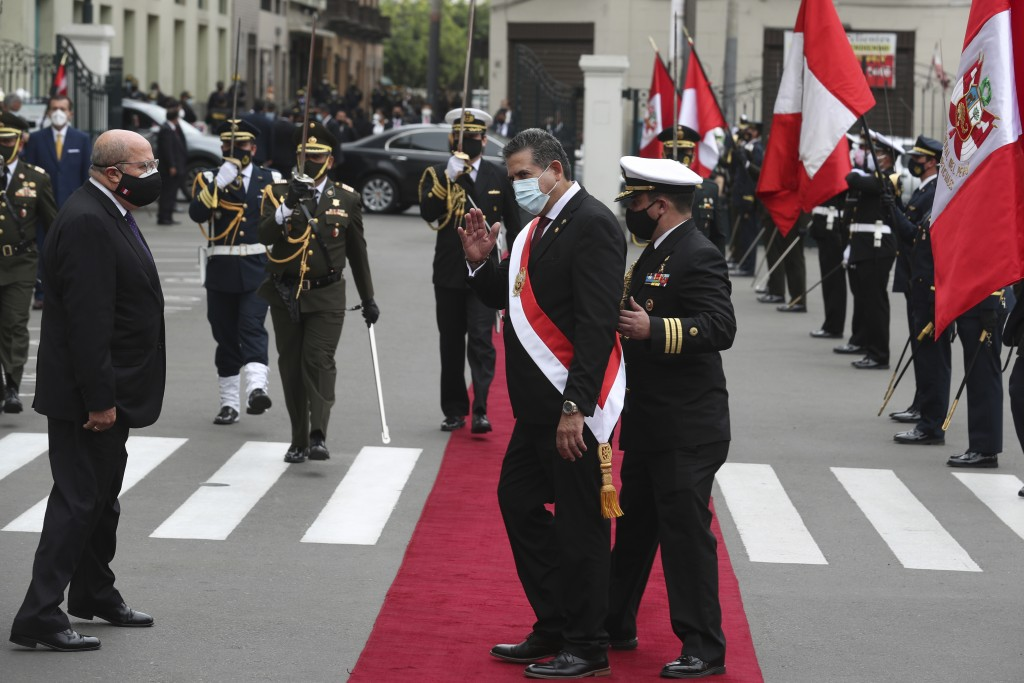 A military aide shows the way to Manuel Merino, the head of Peru's legislature,  after he was sworn-in as Peru's new president, replacing Martín Vizca...