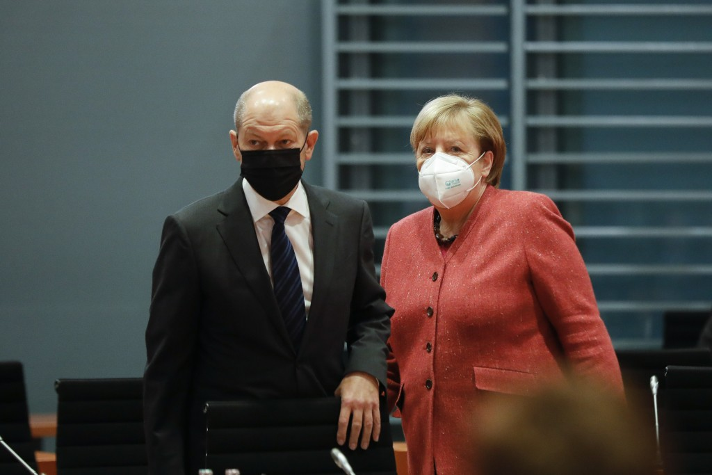 German Chancellor Angela Merkel, right, and German Finance Minister Olaf Scholz arrive at the weekly cabinet meeting of the German government at the c...