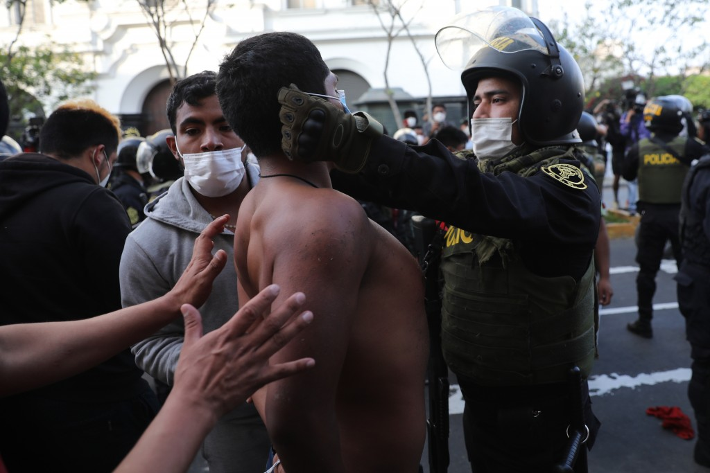 A police officer places a protective face mask on a protester who was detained near Congress where lawmakers swore-in a new president after voting to ...