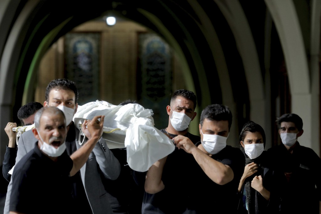 Mourners carry the body of a person who died from COVID-19 at the Behesht-e-Zahra cemetery on the outskirts of Tehran, Iran, Sunday, Nov. 1, 2020. The...