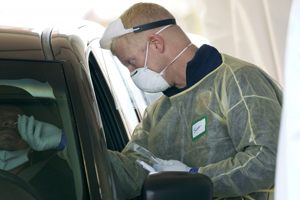 FILE - In this Oct. 28, 2020, file photo, a worker wearing gloves, a face shield, a mask, and other PPE administers a COVID-19 test at a King County c...