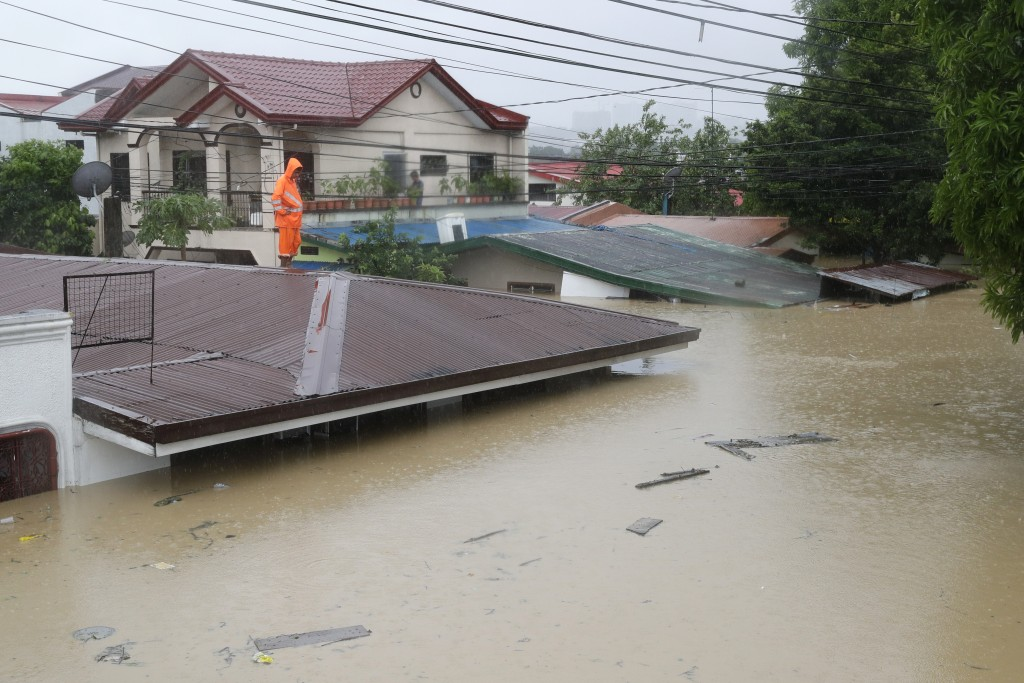 A man stands on the a roof as floods continue to rise in Marikina, Philippines due to Typhoon Vamco on Thursday, Nov. 12, 2020. A typhoon swelled rive...