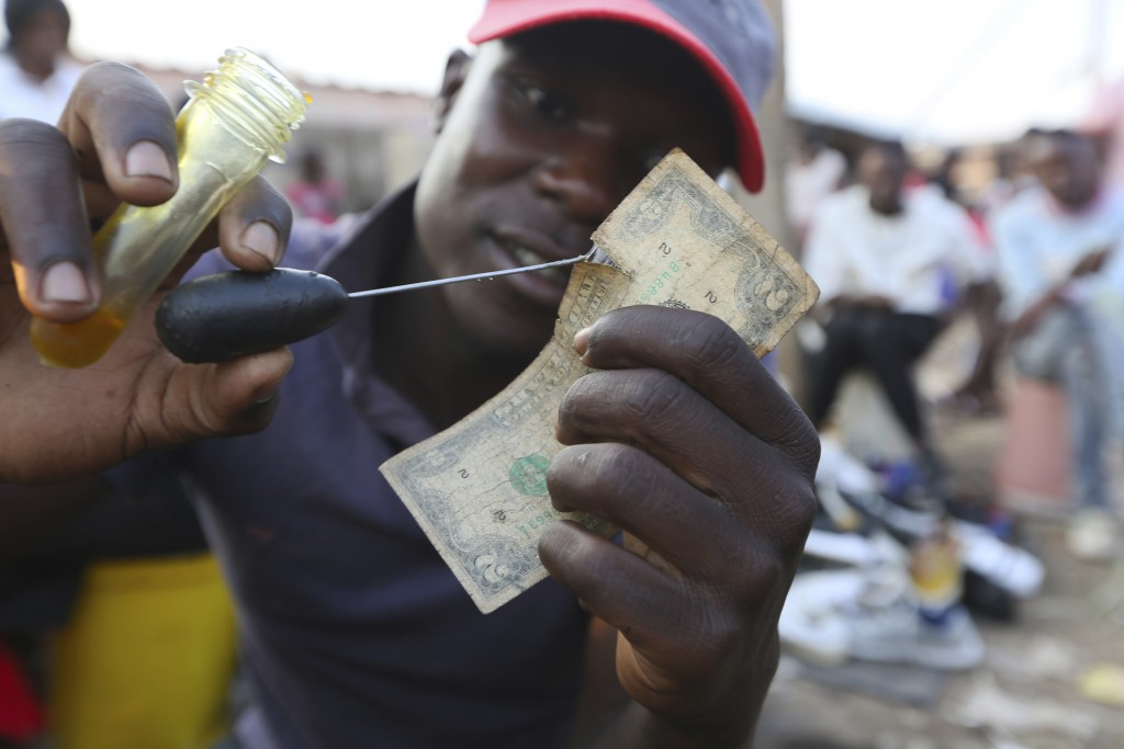 A currency trader mends an old and worn 2 dollar bill at a busy market in Harare, in this Monday, Oct, 26, 2020 photo. Worn out or shredded by rats, o...