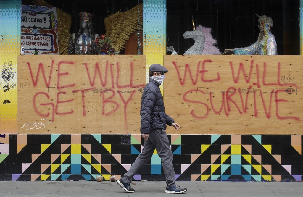 FILE - In this April 18, 2020, file photo, a man wears a face mask while walking past signs posted over boarded-up windows of a store in the Haight-As...
