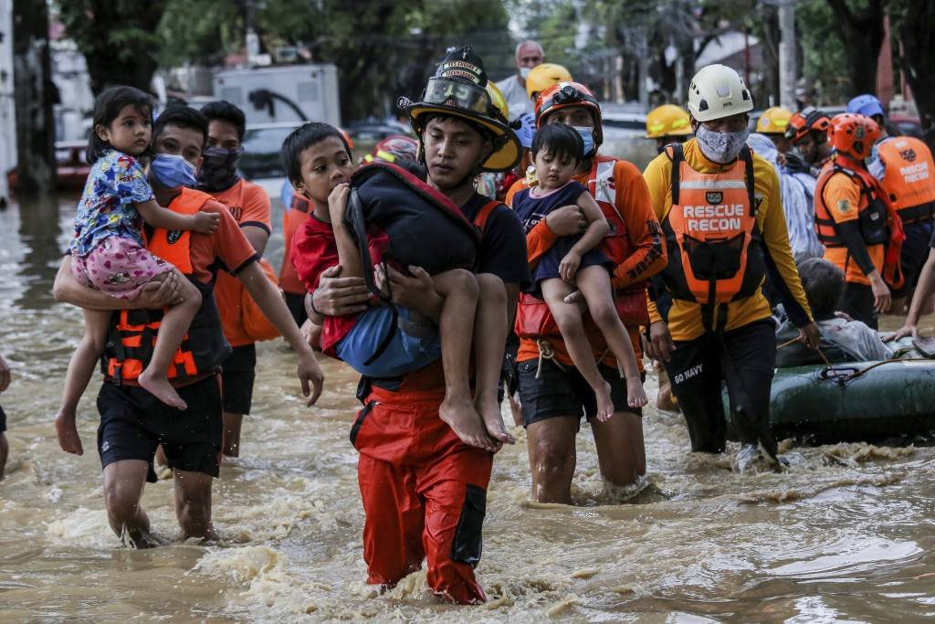 Rescuers carry children out from a flooded street due to heavy rains brought by Typhoon Vamco in Providence village in Marikina City, east of Manila, ...