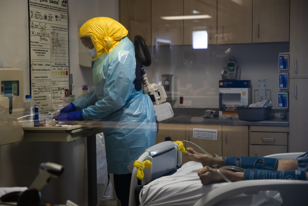 FILE - In this July 21, 2020, file photo, a nurse assists a COVID-19 patient at El Centro Regional Medical Center in El Centro, Calif. In November 202...