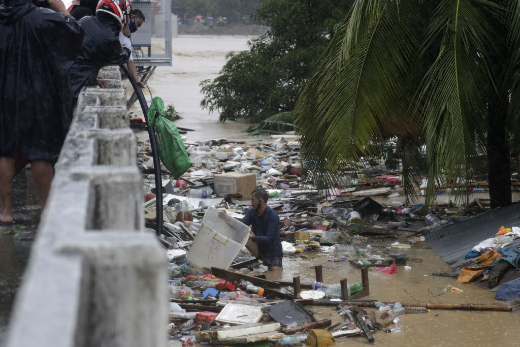 A resident tries to save belongings as floods continue to rise in Marikina, Philippines due to Typhoon Vamco on Thursday, Nov. 12, 2020. A typhoon swe...