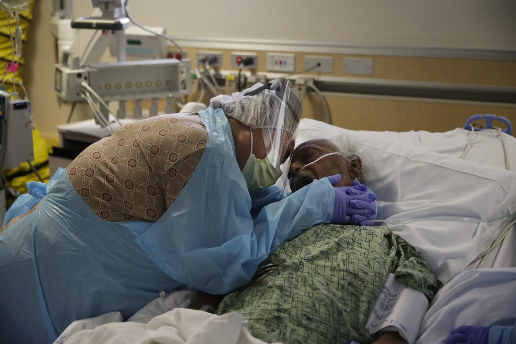 FILE - In this July 31, 2020, file photo, Romelia Navarro, 64, weeps while hugging her husband, Antonio, in his final moments in a COVID-19 unit at St...