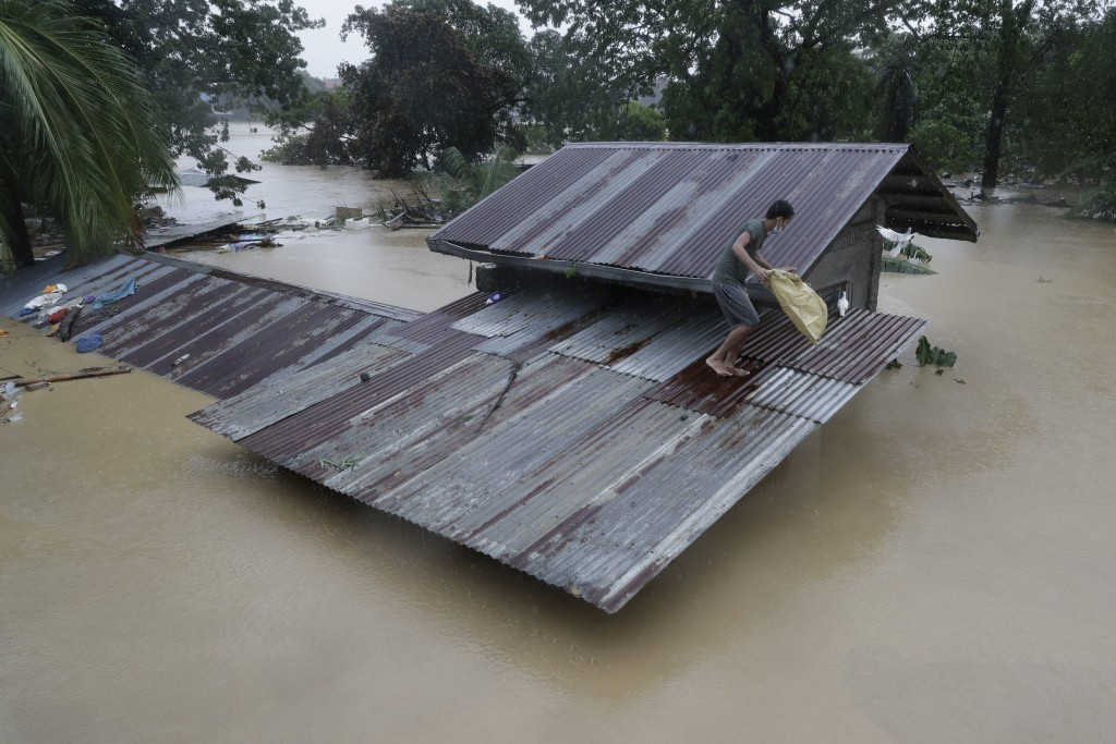 A resident walks on their roof as he tries to rescue his pigeons as floodwaters continue to rise in Marikina, Philippines, due to Typhoon Vamco on Thu...
