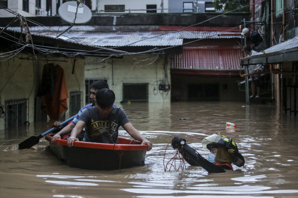 Rescuers assist trapped residents during a rescue operation in Providence village in Marikina City, east of Manila, Philippines, Thursday. Nov. 12, 20...