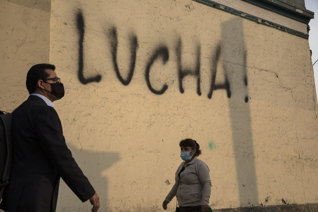 Pedestrians walk past a wall spray-painted by an anti-government protester with the Spanish word for fight, just a block from the Justice Palace where...