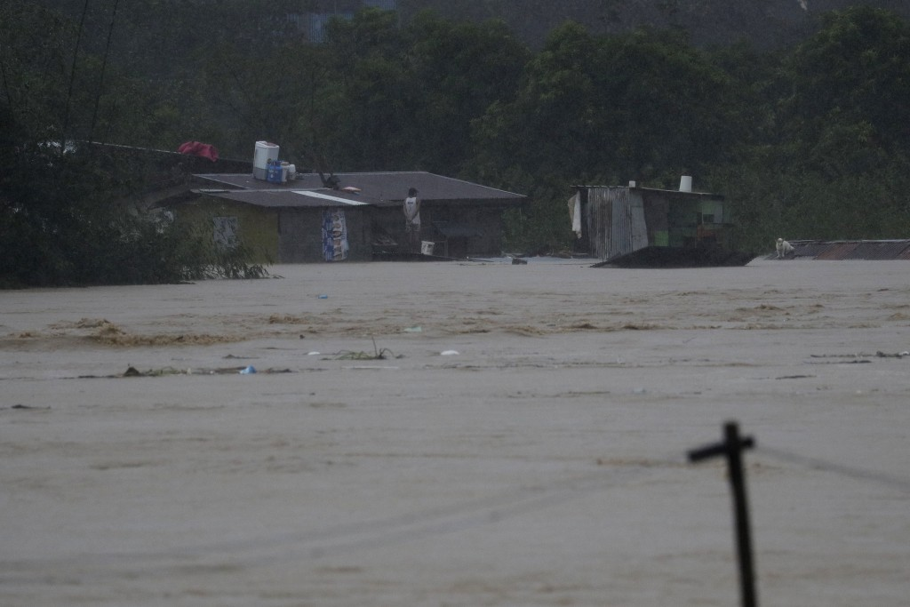 A residents trapped on their roof await rescuers as floods continue to rise in Marikina, Philippines due to Typhoon Vamco on Thursday, Nov. 12, 2020. ...