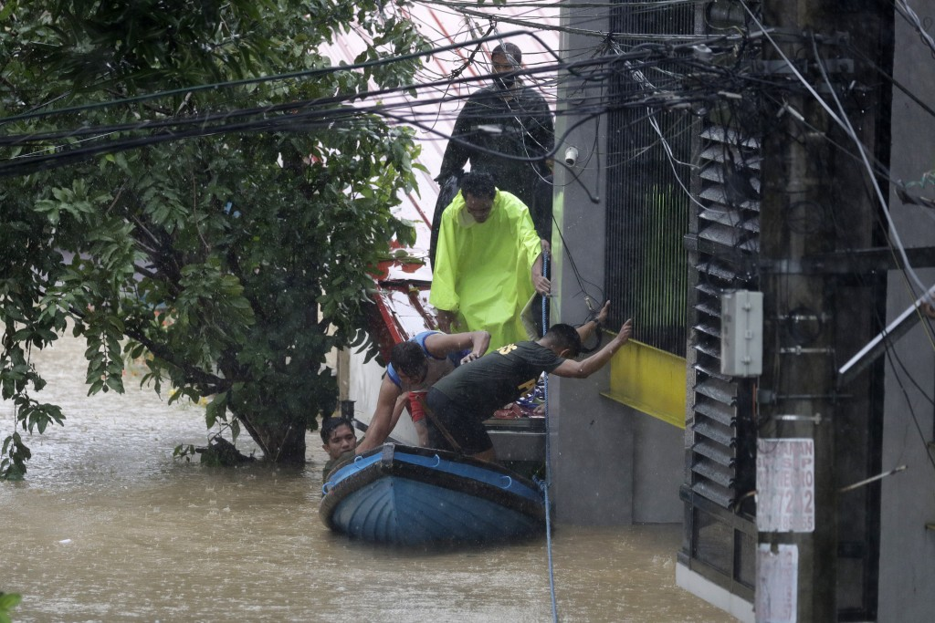 Residents trapped on their roofs board a small raft as they are evacuated as floods continue to rise in Marikina, Philippines due to Typhoon Vamco on ...