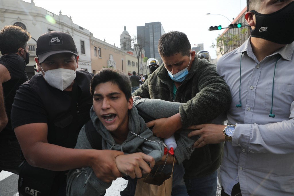 Plainclothes policemen detain a supporter of ousted President Martin Vizcarra near a police barricade, preventing marchers who are refusing to recogni...