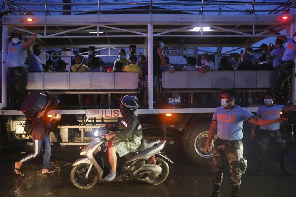 Trapped residents ride a police truck after a rescue operation in Providence village in Marikina City, east of Manila, Philippines, Thursday. Nov. 12,...