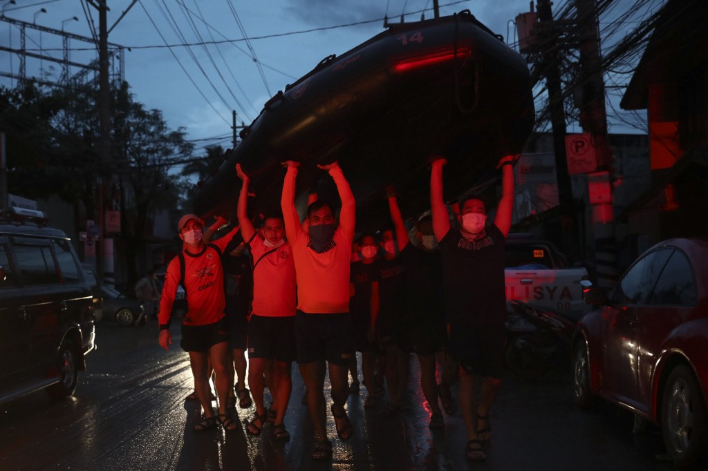 Rescuers carry a rubber boat to save trapped residents after flood waters inundated their homes due to Typhoon Vamco in Providence village in Marikina...