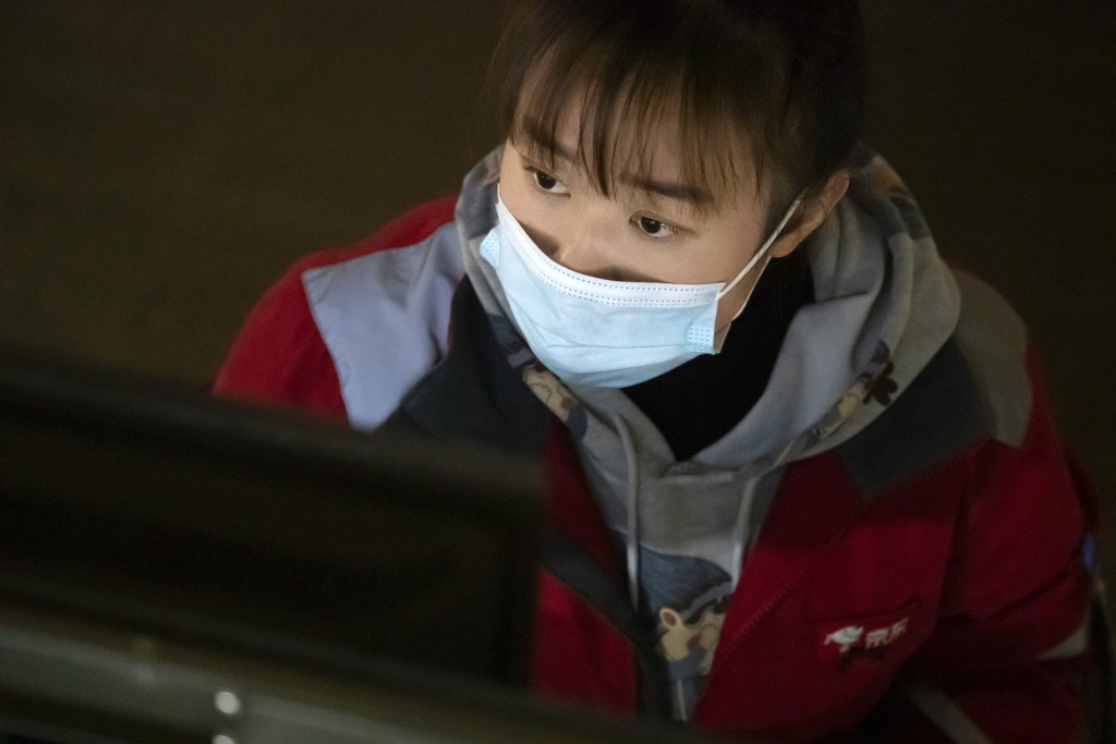 An employee looks at a computer terminal as she monitors an automated parcel handling line at a warehouse for online retailer JD.com in Beijing, Wedne...