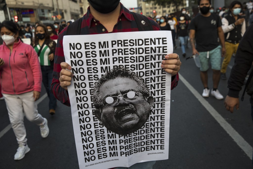 """A man holds a poster with an image of Peru's newly sworn-in President Manuel Merino with a message that reads in Spanish: """"He is not my president,"""" du..."""