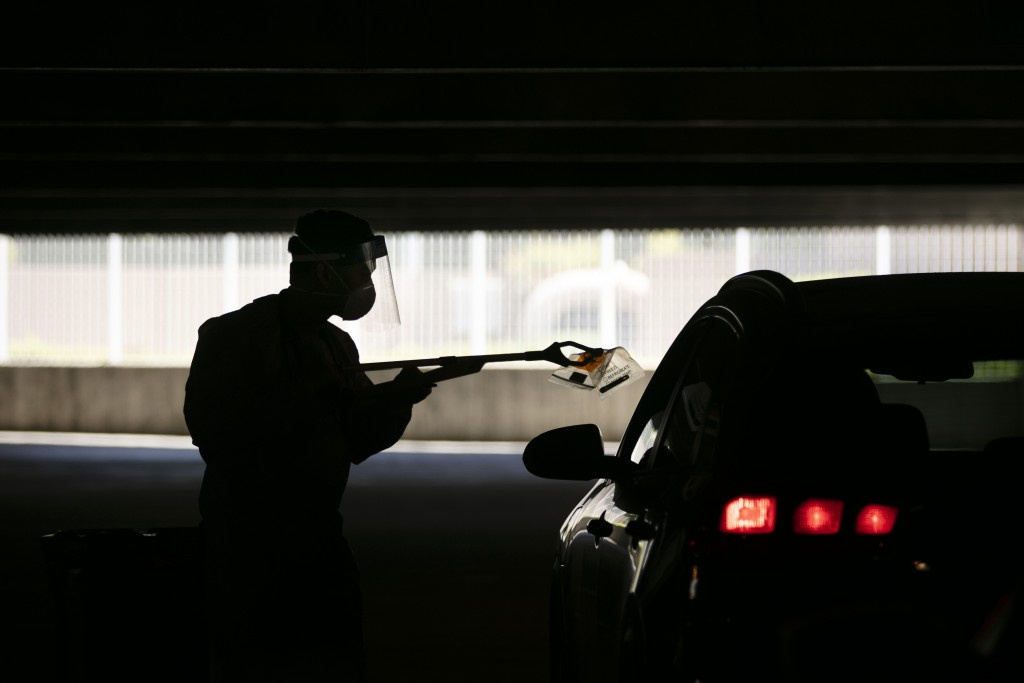 FILE - In this July 16, 2020, file photo, a physician assistant uses a grabber to collect a nasal swab sample at a COVID-19 drive-thru testing site se...
