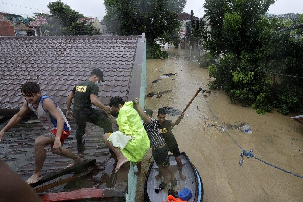Police rescue residents as floods continue to rise in Marikina, Philippines due to Typhoon Vamco, Thursday, Nov. 12, 2020. A typhoon swelled rivers an...