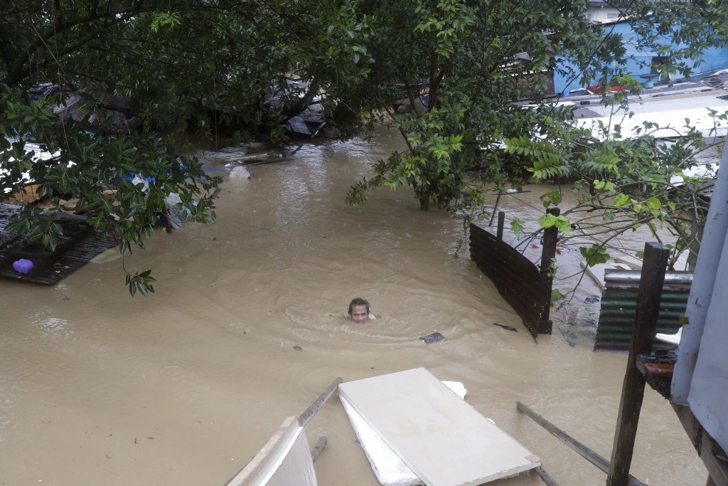A man swims in neck deep floodwaters as it continues to rise in Marikina, Philippines, due to Typhoon Vamco on Thursday, Nov. 12, 2020. A typhoon swel...