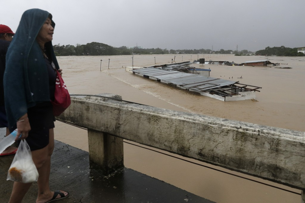 A woman looks at submerged structures at a swollen river as floods continue to rise in Marikina, Philippines due to Typhoon Vamco on Thursday, Nov. 12...
