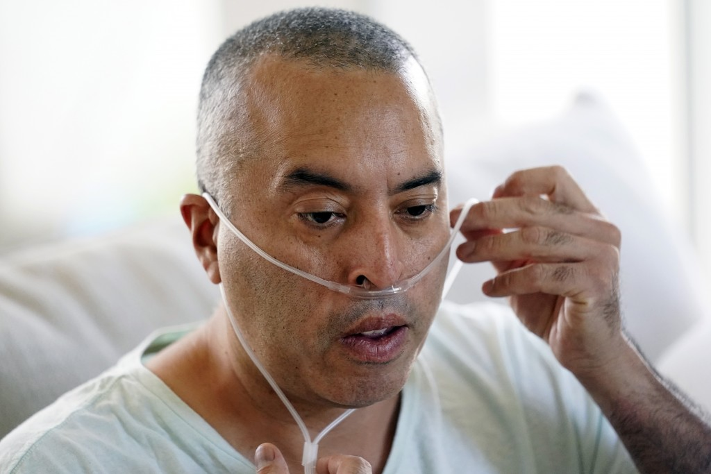 Antonio Gomez breathes with the help of an oxygen tank at home, Wednesday, Nov. 11, 2020, in Simi Valley, Calif. Gomez is recovering at home after a t...