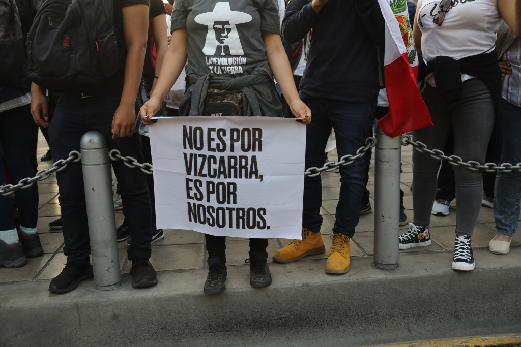 """A woman, holding a sign with a message that reads in Spanish: """"It's not for Vizcarra, it's for us,"""" joins others outside the Justice Palace where peop..."""